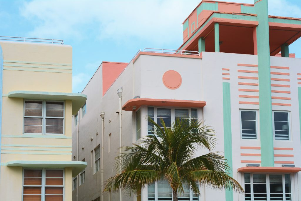 An image of a building showcasing the art deco style. It is a fun, pink, ornamented building with a palm tree in front.
