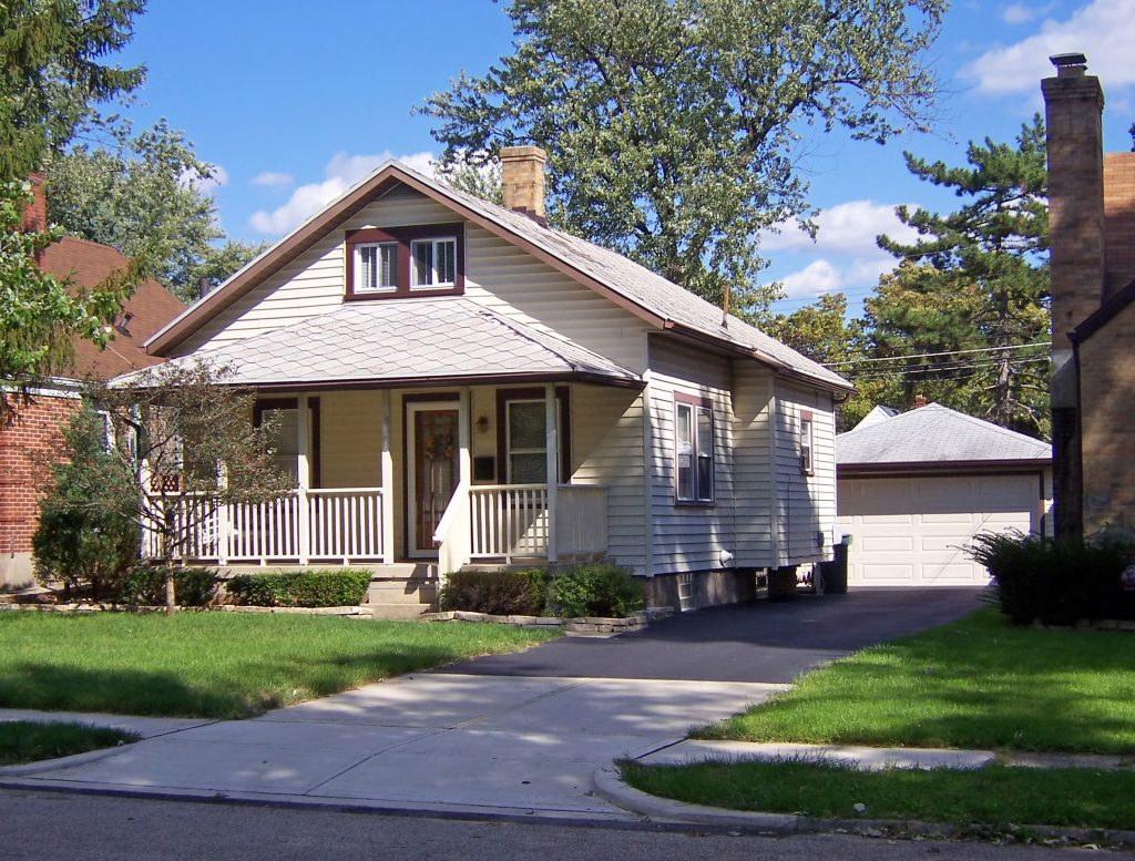 An image of a standard bungalow home. It is a one and a half story home with white siding, a porch, and a garage in the back.