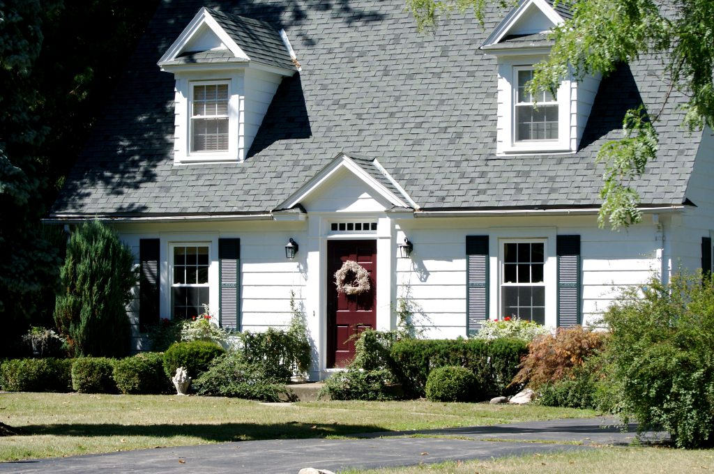 An image of a cape cod home. It is a small, white home with four symmetrical windows in front and a burgundy door.