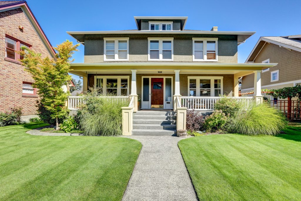 An image of a craftsman home. It is a square, two and a half story home with a large porch and front steps.