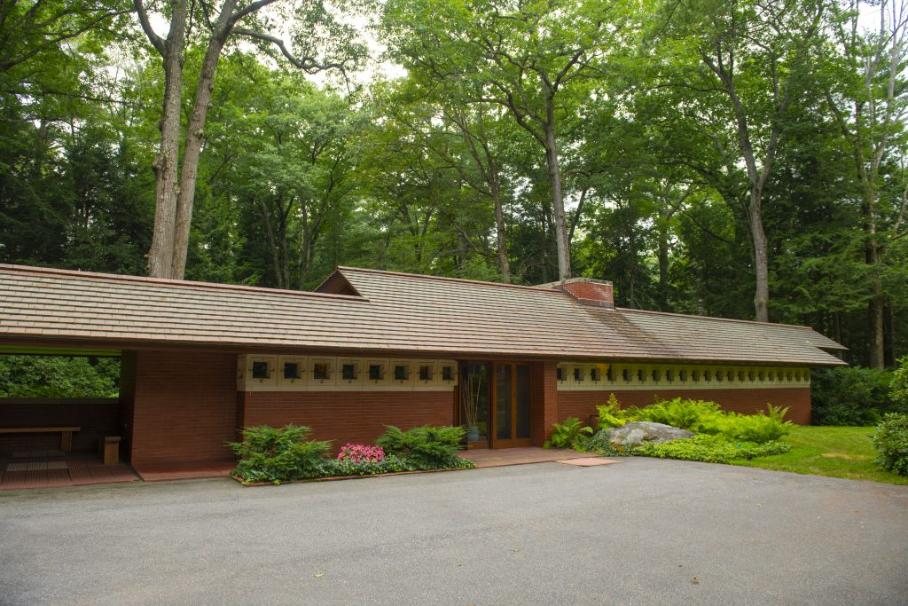 An image of a prairie school home designed by Frank Lloyd Wright. The front of the home is a very long, narrow, one story wide strip with a low slanting roof. The home is made out of brick; the upper third of the home is white brick, with square gaps that make a pattern. The home is surrounded by trees or forest on three sides.
