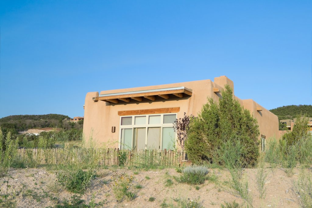 An image of a pueblo style home. This single family home is one tall story, made out of a light clay colored material. There is a block of windows out of the side of the house we see. It looks like a back yard, as there is a low fence made out of wooden posts. It is set in a desert, arid landscape somewhere.