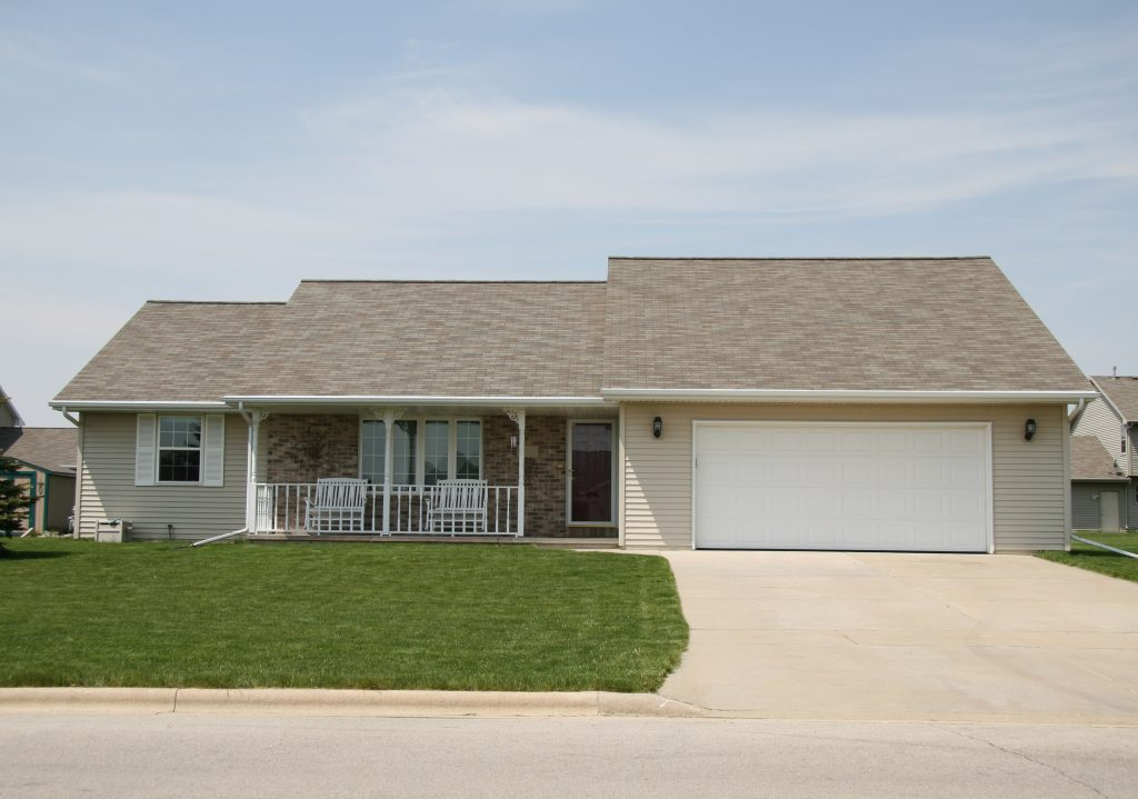 An image of a suburban ranch home. There is a small patio with outside the centrally placed front door, with an attached garage taking up the right half of the front facade. The home is made out of both brick and siding.