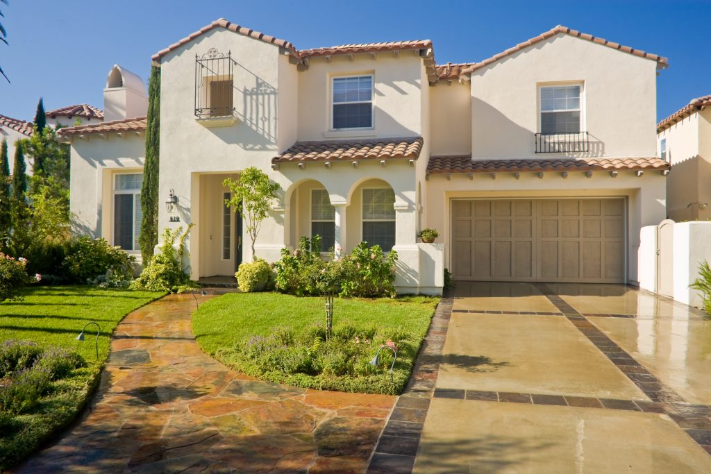 A two-story spanish revival home. The home is a light color clay, with a terra-cotta style clay roof. The second story windows have wrought iron protrusions from them for ornamentation. The driveway and front walkway are a collage of stone.