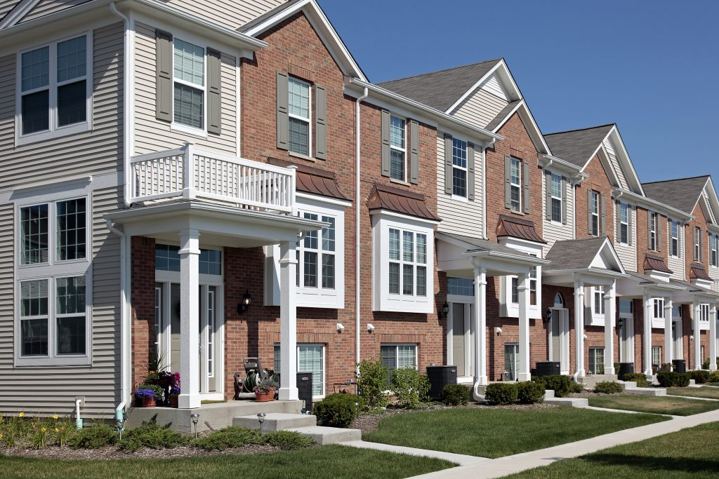 A row of two or three story townhomes. The townhomes are each half brick and half siding, with covered entryways.