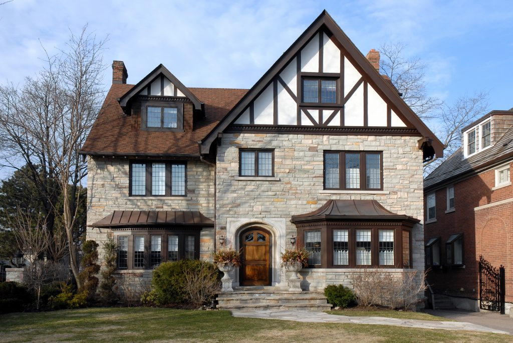 A tudor style home. The home is a large three story home, with a big, heavy, wooden front door. The first two stories are made out of brick, and the top story is colored white with dark brown wooden crossbeams attached in a simple pattern. There are two sets of bay windows that are the same color brown- one on the left side and one on the right side of the house.