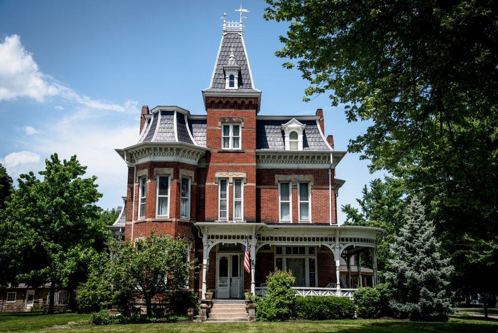 A victorian style house. The house is at least three stories, with a central tower extending above the front door that is a story above the rest. There is a large wrap around porch. The house is made out of brick, and has a grey shingled roof. The roof is highly creative and has several different shapes. The windows are all very thin and tall.