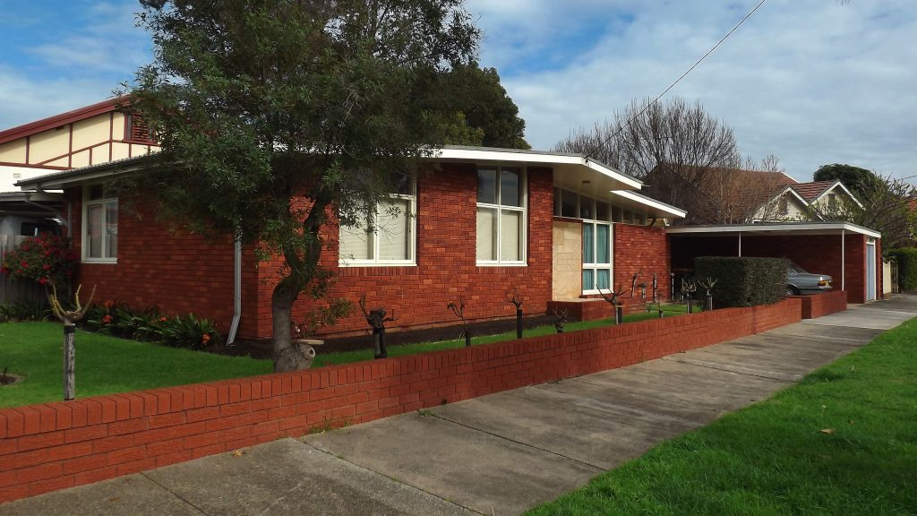 An image of a mid century modern home. It is a long, one story home made out a deep red brick. The roof slants from side to side, and has a very low pitch. There is a covered car port on the right side, and lots of oddly shaped windows throughout the house.