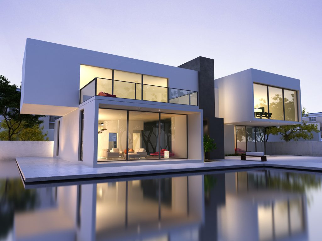 An image of a modern style house. The mostly-glass house is two stories, with each story being two long boxes that go in opposite directions. The house sits on a white concrete slab that is surround by water on three sides. You can see most of the home's interior through the full length glass windows.